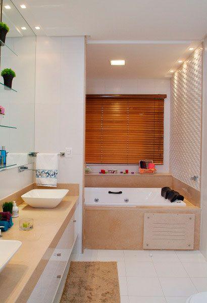 Para a suíte do casal, a arquiteta Maristela Bernal fez tudo para dois: banheira dupla e bancada com duas cubas. Para que a parede da banheira fosse destacada, ela foi revestida com um mosaico em relevo e as janelas cobertas com persianas de madeira.