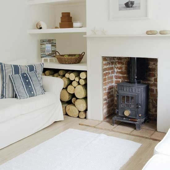 Practical shelving makes the most of the alcove space in this living room, with a large space on the bottom shelf to store logs to fuel the traditional wood-burning stove. Light wooden flooring is teamed with a fresh white rug to match the sofa. Nautical-style cushions and other seaside accessories complete the coastal look.