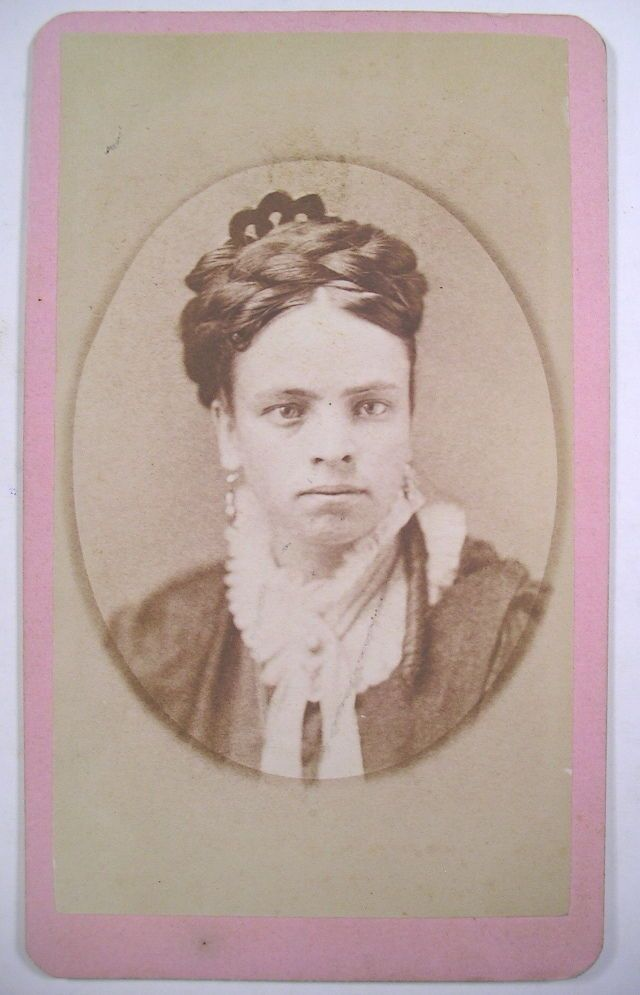 Pretty young woman wearing her hair in a thick coronet braid with a scalloped openwork comb placed behind. Carte de visite 1880s