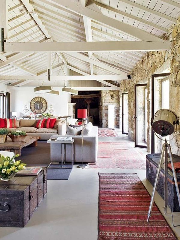 Classic kilim rugs add color to the textured, neutral stone architecture in this Portuguese home by interior designer Marta Espregueira Mendes. Photo via Lakber Magazin.