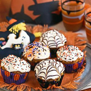Top half of these spiced pumpkin cupcakes with Halloween sprinkles and half with melted chocolate drizzled to look like spider webs.