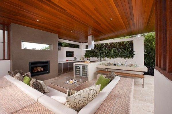 salon extérieur avec cheminée et accès vers le jardin