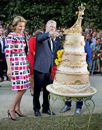 The King and Queen cut the very large cake in the park.
