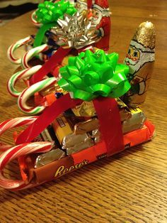 "French Hen Farm ;""Start with a full size candy bar and hot glue the candy cane sled rails (as you see at the bottom of this picture). I used my two favorites: Reese's and Kit Kats. I secure the rails with a little extra hot glue on the sides. Then pile up the mini candy bars. Add a pretty ribbon and a little bow. I finished mine off with these cute little chocolate Santa's I found at Aldi's."""
