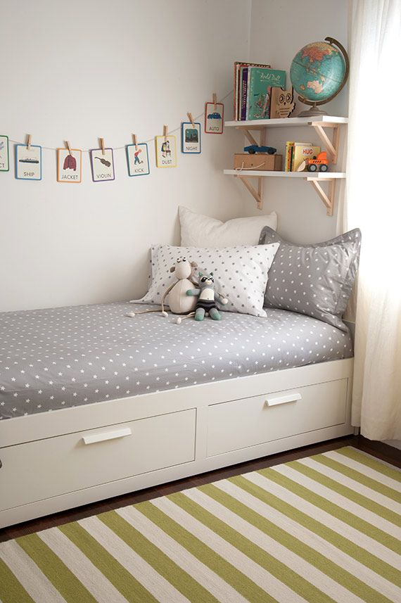 simplicity and neatness are in order with underbed storage, over the bed shelving, and a crisp, clean color palette.