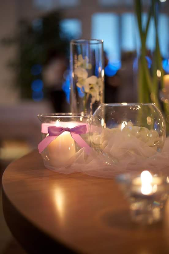 addobbi centrotavola, in vetro; sulla sinistra particolare con candela e fiocco colorato