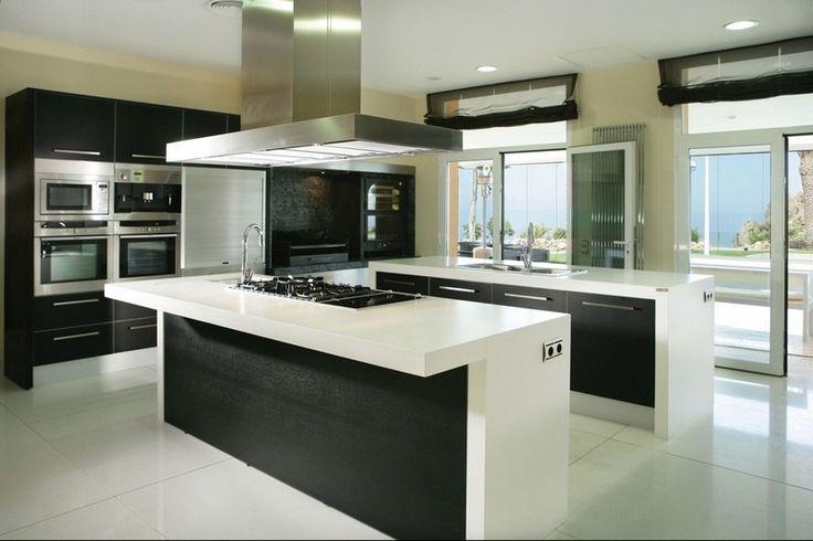 cuisine blanche et noire professionnelle avec appareils encastrés et hotte aspirante inox