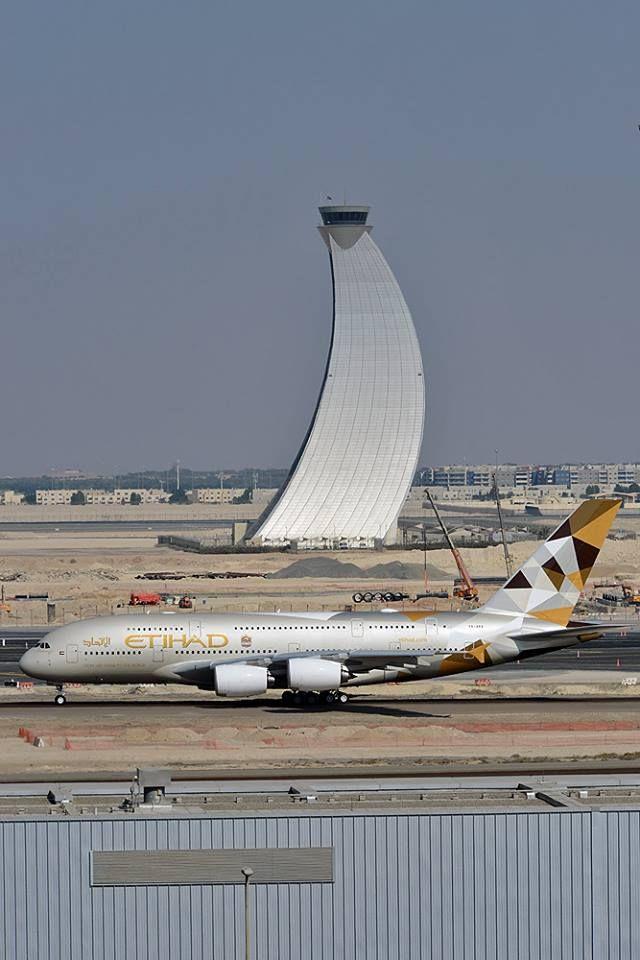Etihad Aerobús de Vías aéreos A380-861 A6-APA pasando delante de una de las Torres de Control del tráfico aéreo líderes mundiales más icónicas en Abu Dhabi Aeropuerto Internacional, diciembre de 2014.