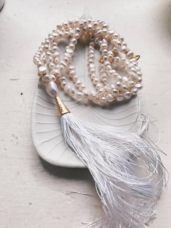 Prachtige ultra luxe bruiloft mala van witte parels en goud. Een dubbele streng van echte parels wordt gecombineerd tot in de perfectie met een cap goud kwast en delicate bladeren.  Deze prachtige ketting is afgewerkt met een 100% zijde, witte kwast.  Perfect voor boho bruiloften.