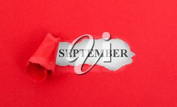 Text appearing behind torn red envelop - September