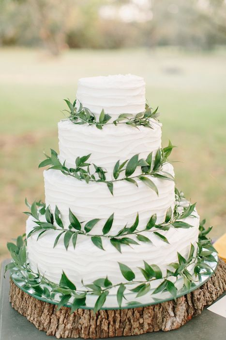 Bolo de casamento com cobertura branca e folhas