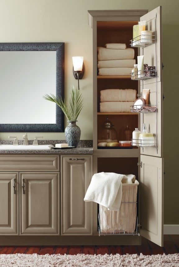 An organized bathroom helps with your morning routine includes a linen cabinet ith a roll out hamper & wire racks on the door for toiletry items.