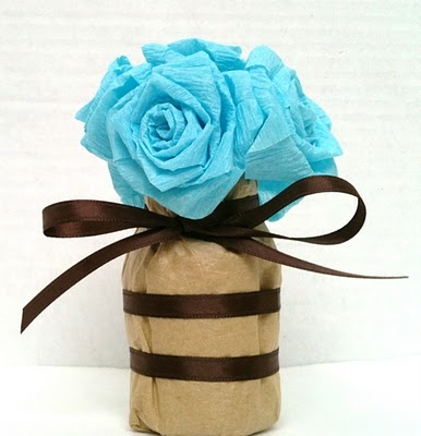 vitamin bottles covered in tan tissue paper.  brown ribbon around the bottles and tie 6 to 8 roses into a bouquet using bread ties.