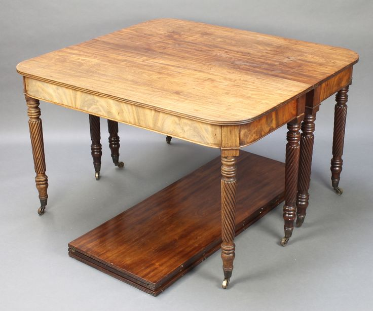 """Lot 973, A George III mahogany extending dining table, raised on 8 spiral turned legs, complete with 3 extra leaves 27""""h x 100""""l x 43""""w est £300-500"""