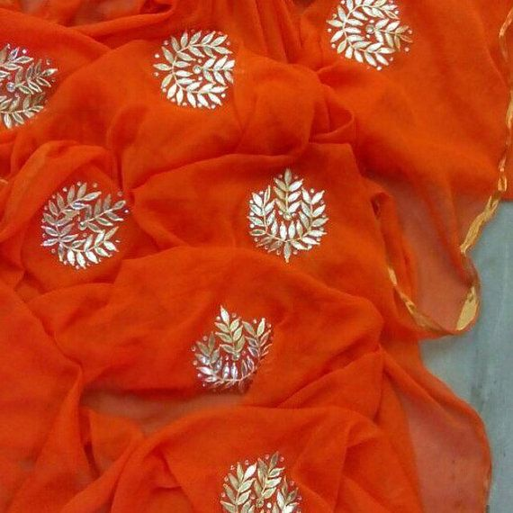 A beautiful and bright orange chiffon saree with handmade Gota Patti motifs. Comes with a matching blouse piece! Perfect for a festival or wedding