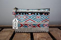 Pochette ethnique Paula avec tissu navajo bleu, blanc, rouge et noir et pompons noirs. Fabriquée dans notre atelier situé à Colmar, en France.