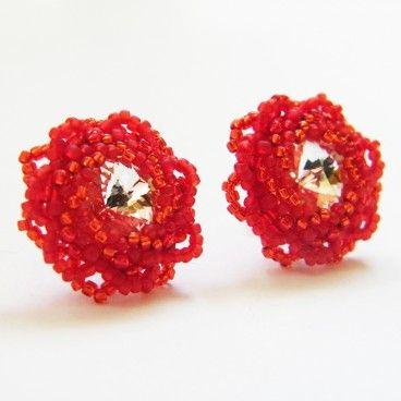 Różyczki crystal Urocze kolczyki wyplecione niezwykle czasochłonną techniką beadingu. Ich serce stanowią kryształy rivoli Swarovskiego w kolorze crystal, które oplotłam najwyższej jakości japońskimi koralikami TOHO w dwóch odcieniach czerwieni. Koraliki układają się wokół kryształów w kształt płatków, czyniąc z kolczyków miniaturowe różyczki.   www.KuferArt.pl