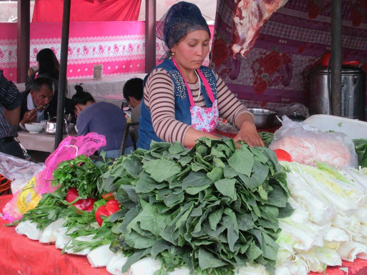 This lady at the Sunday livestock market in a suburb northwest of Kashgar, Xinjiang, China, is preparing greens.