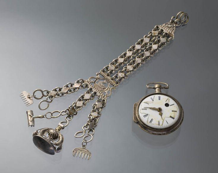Zilveren horloge aan een zilveren horlogeketting, gedragen in het dorp Aagtekerke op het eiland Walcheren. Aan de horlogeketting hangen een  signet en een paar miniatuurtjes: twee kammen en een roskam. 1850 #Zeeland #Walcheren