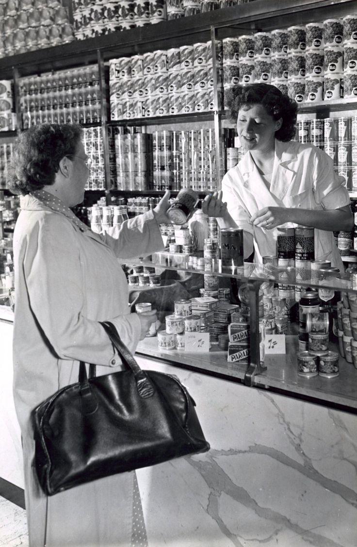 Overleg over de aanschaf van een blik groente tussen de medewerkster van de kruidenierswinkel en een klant met een boodschappentas, Nederland, 1950.