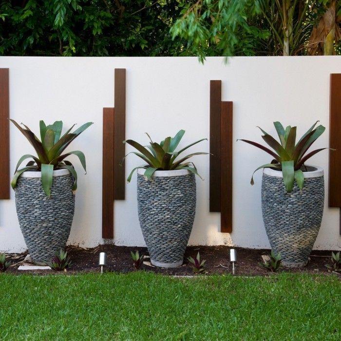 Три одинаковых кашпо цилиндрической формы, сделанные из цельного камня, и декорированные мелкой галькой.