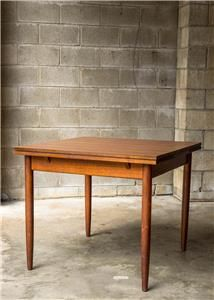 Parker Furniture table c1963. Solid teak construction with teak laminate top. Draw leaf extension and the now infamous legs