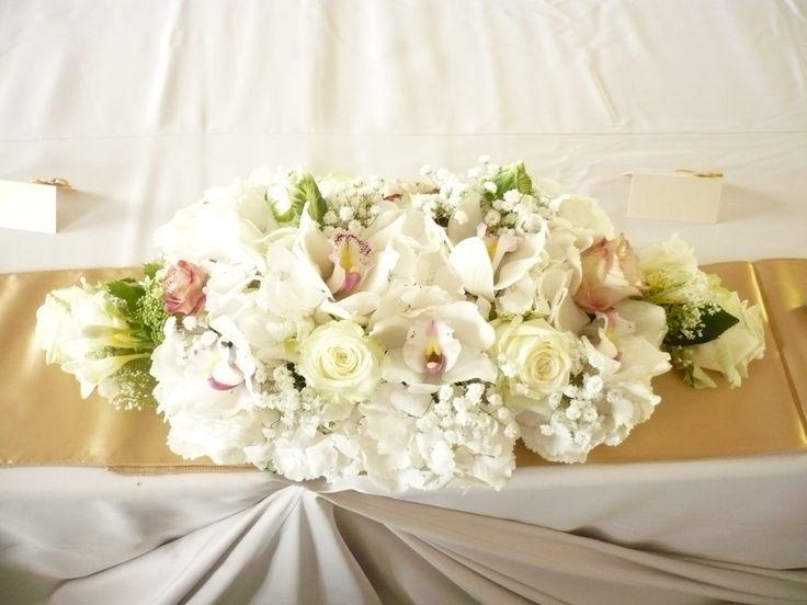 A fehér és a világos pasztellszínek csodás kompozíciója köszön vissza az esküvői főasztal virágdíszében, igazi letisztult képet alkotva