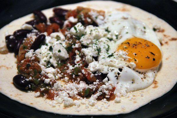 Huevos rancheros  Pour 2 personnes      1 petite tomate     1/2 oignon     1/2 piment vert     2 gousses d'ail     1/4 c. à c. de sauce piquante     1/2 c. à c. de cumin     200 g  de haricots rouges, égouttés et rincés     2 œufs     2 tortillas de maïs     50 g de feta émiettée     2 tiges de coriandre fraîche hachée     7 cl d'eau     Sel, poivre     Huile d'olive