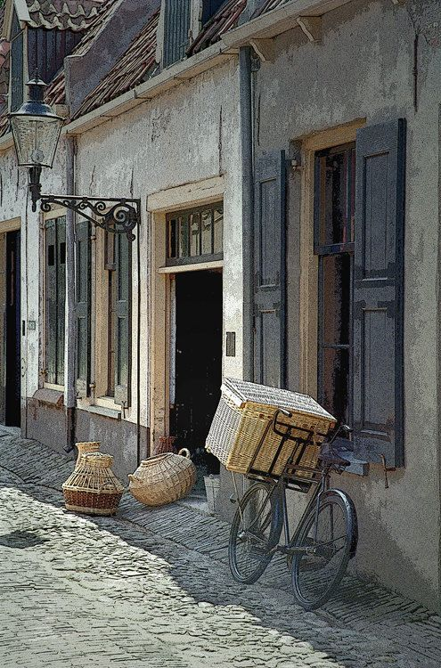 Photograph of a Bicycle with a basket on a street in a village by the Zuider Zee in the Netherlands.