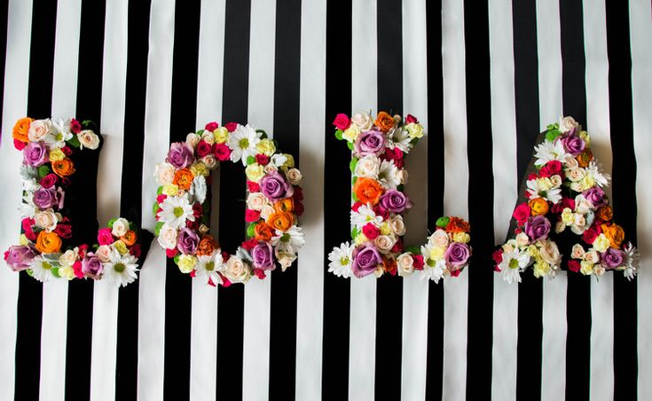 Floral hanging letters on black and white stripes. Baby shower flowers. Purple…