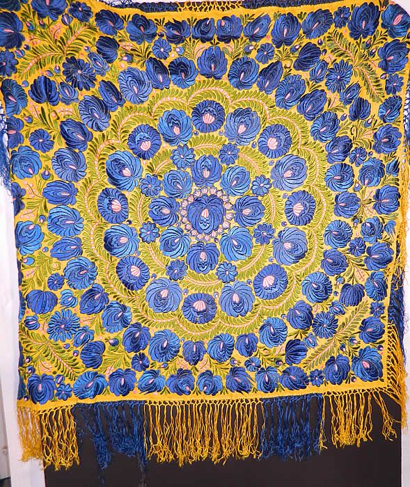 Antique Matyo Hungarian Folk Embroidery Fringe Large Square Shawl Tablecloth There is a floral vine leaf design densely embroidered onto the fabric in a circular pattern, with hand knotted two tone yellow and blue silk fringe trim edging. The embroidery work is exquisitely done with wonderful workmanship.