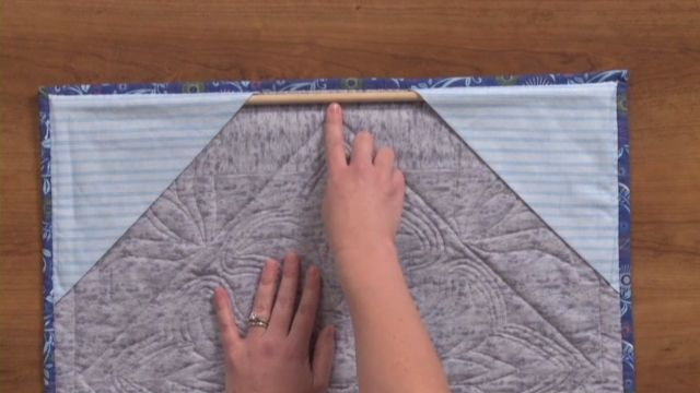 Learn how to hang a quilt on your wall with just one hook or nail. Follow the steps in this instructional video from National Stitching Circle.