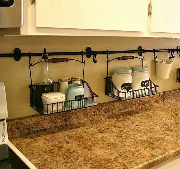 Small spaces require out of ordinary ideas...use curtain rods and hanging baskets to keep items off the counter. Works well in bathrooms too!