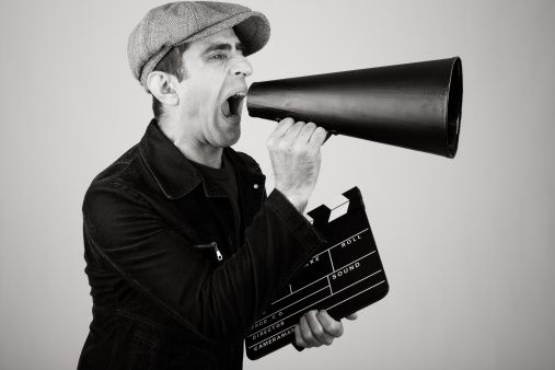 Film Director Shouting With Megaphone While Holding Film Slate