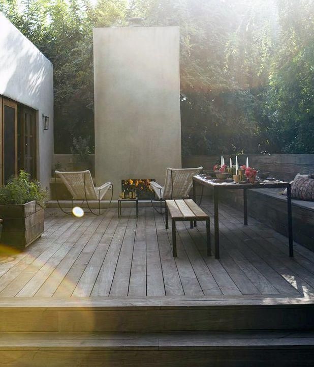 eldstad, platsbyggda bänkar, växter bakom stödmur, upphöjt altandäck