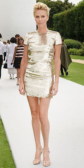 CHARLIZE THERON The very definition of statuesque (the woman looks like an Oscar!), Charlize stuns in a sparkly gold Dior mini that makes her legs look miles long at the runway show for the brand in Paris.