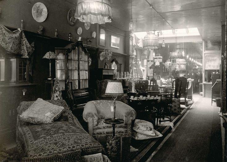Interieur van warenhuis van de firma Laeb in Den Haag, waar men op afbetaling kan kopen. In beeld oa. een bed, fauteuil, kasten, lampen en een eethoek. Nederland, 1916.