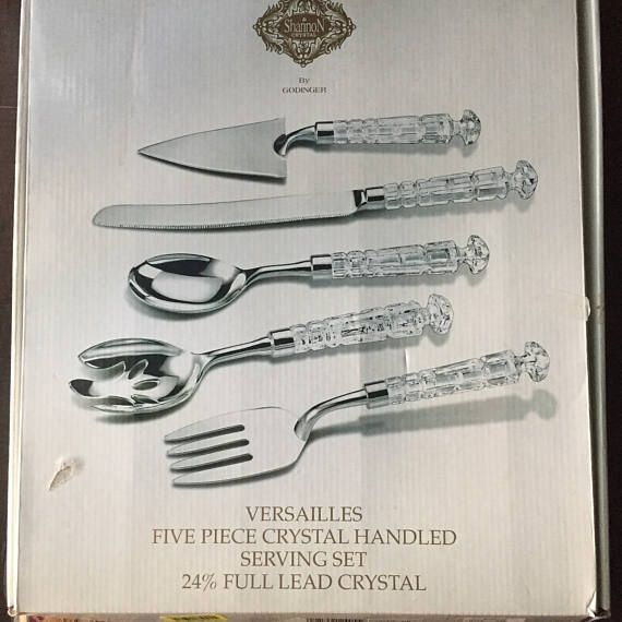 For consideration this Shannon by Godinger 5-piece set of Serving utensils were made with 24 percent Full Lead Crystal. They feature the Versailles pattern and are in excellent condition. In my opinion the set looks like it was never used. The set includes 1 open spoon, 1 cake