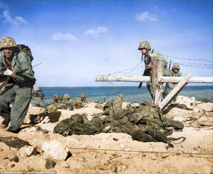 A group of fighters, led by a Marine with a wounded hand, charging from the shore around opened barbed-wire entanglement to battle firmly entrenched Japanese in pillboxes on Tarawa. The photos were restored by colouriser RoystonLeonard, from Cardiff