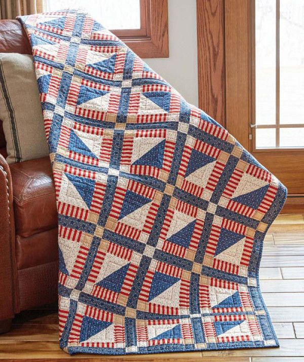 A simple framed triangle square block creates this throw size quilt in red white and blue prints. This easy quilt pattern is perfect as a Quilt of Valor!