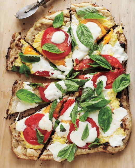 Grilled Pizza with Pureed corn + garlic + olive oil, Tomatoes, Parmesan Cheese, and fresh mozzarella, & before serving topped with fresh basil.