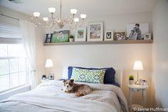 quarto decorado, cachorro em cima da cama, prateleira alta sobre a cama com aquadros e fotos