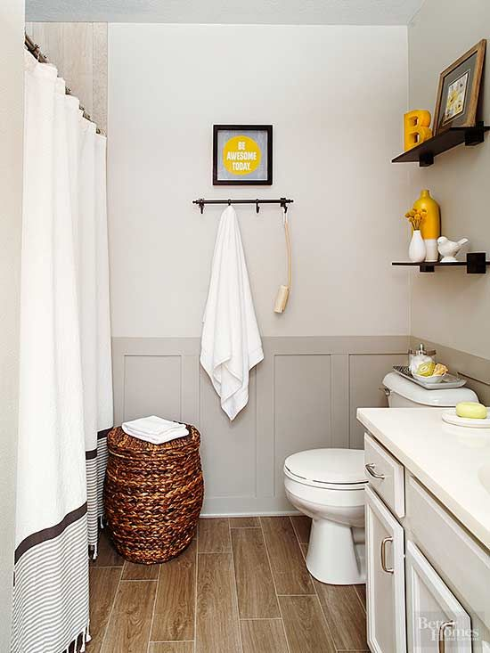 Take traditional shades like tan and gray to the next level with a pop of citrus color. Lemony accents brighten this otherwise monochromatic bathroom. Rich gray board and batten provides depth to the room and sets off light khaki-colored walls./