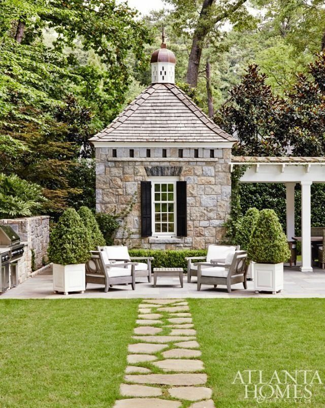 A stone pathway leads to the perfect outdoor patio and charming stone poolhouse.