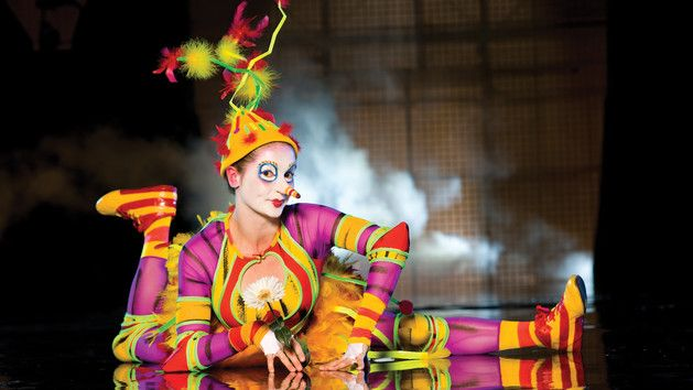 Female performer dressed as a clown with legs extended and arms at 90-degree angles at Cirque du Soleil – La Nouba