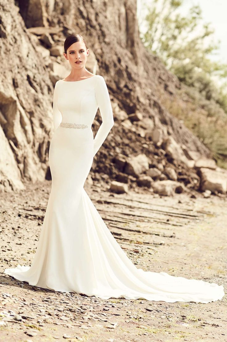 Mikaella Bridal wedding dress | Style 2105, Crêpe Wedding Dress. Bateau neckline gown with long sleeves. Removable Crêpe belt with beaded appliqué. Fit and flare Crêpe skirt. Fabric covered buttons down center back of skirt to hem.