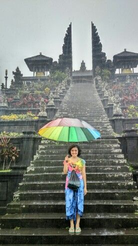 It would be perfect if you could took a picture in the greatest temple in Bali using colorful umbrella in a rainy day.