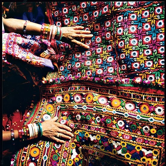"Near the Shaam-e-Sarhad resort in Hodka, India, Virabal Achaar Harijan displays her family's embroidery. The stitchwork is called paako, or ""solid,"" and often includes small mirrors."