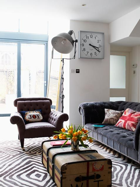 Grand scale for small living area- large pieces, vintage stage lilght, oversized wall clock and large patterned rug.