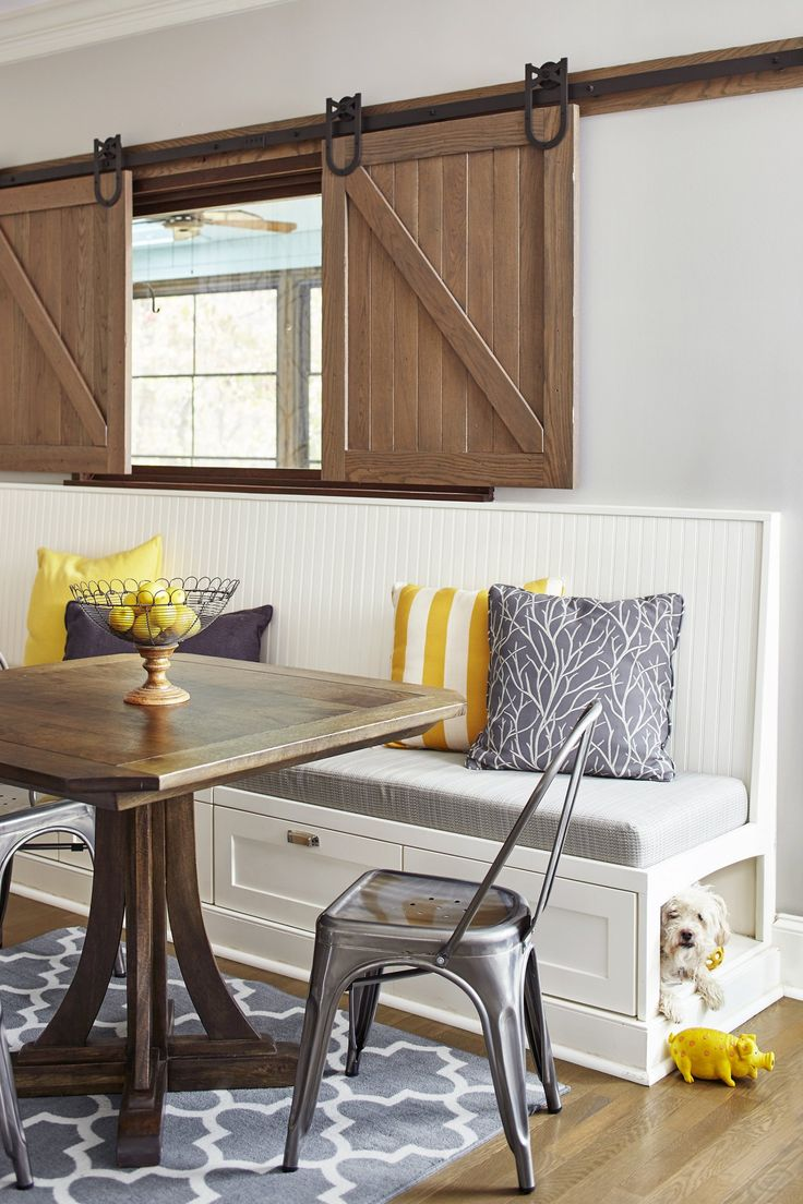 Barn-door-inspired shutters warm up the white walls in this banquette area. And a niche beneath provides a cozy spot for the family dog.